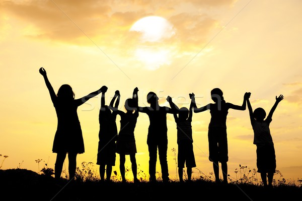Group of happy children standing on meadow at summer sunset Stock photo © zurijeta