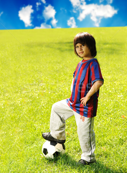 Young excited boy standing with the  ball in the grass outdoors Stock photo © zurijeta