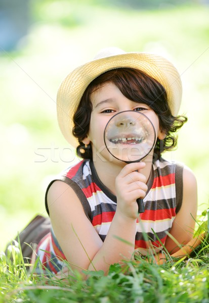 Happy kid exploring nature with magnifying glass Stock photo © zurijeta