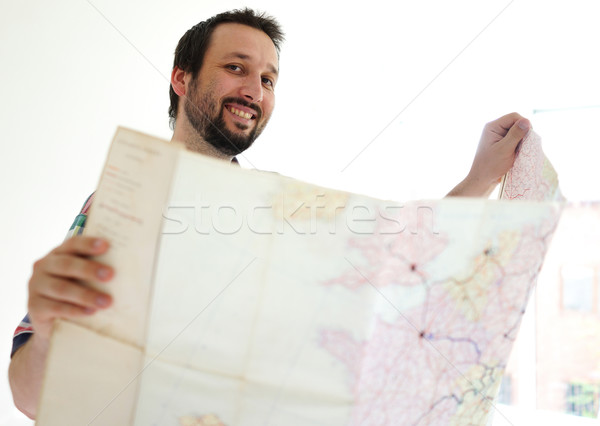 Adult man with bear holding big paper map and looking for right  Stock photo © zurijeta