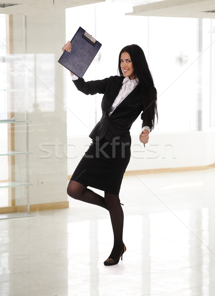 Fullbody of a young happy business woman in modern office Stock photo © zurijeta
