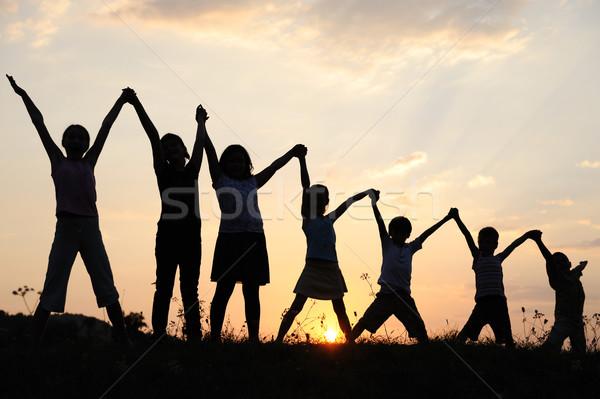 Silhouet groep gelukkig kinderen spelen weide Stockfoto © zurijeta