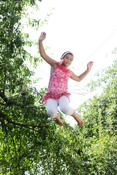 Kid jumping high in nature surrounded by trees Stock photo © zurijeta
