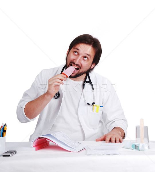 Young male doctor is eating ice cream on his desk in office Stock photo © zurijeta