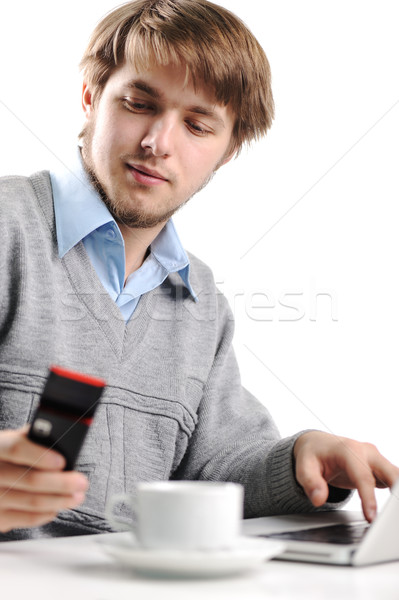 Young man writting short message on cell phone, working on laptop and drinking coffee Stock photo © zurijeta