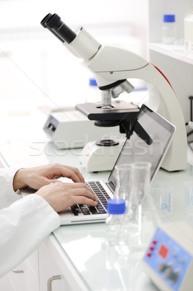 Working in lab with microscope and writing results on laptop, closeup Stock photo © zurijeta
