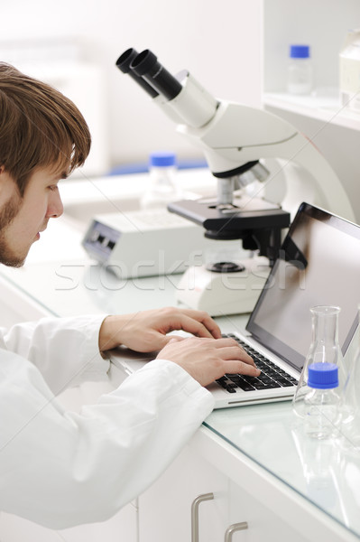 Jovem masculino investigador olhando microscópio escrita Foto stock © zurijeta