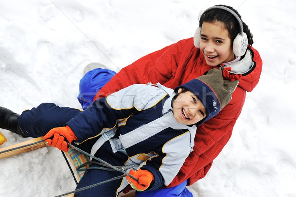 Kids sliding sledge in the snow Stock photo © zurijeta
