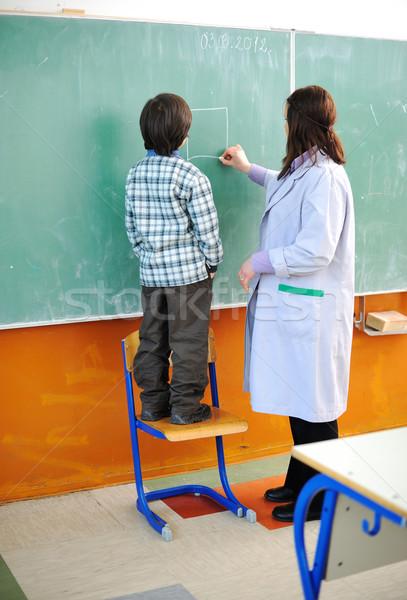 Kid and his teacher in classroom Stock photo © zurijeta