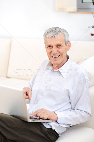 Senior good looking man with laptop at home Stock photo © zurijeta