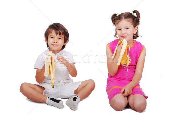 Two little children siting and eating banana Stock photo © zurijeta