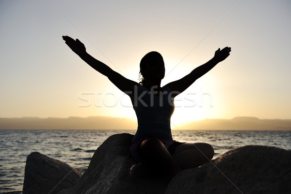Silhouette of a beatiful female meditating on a rock by the sea Stock photo © zurijeta