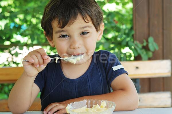 Stock photo: Cute little kid eating ice cream and enjoying