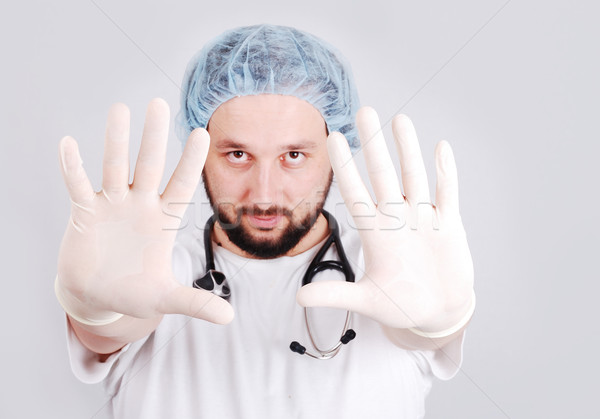 Young male doctor with hands in front and surgery gloves on Stock photo © zurijeta