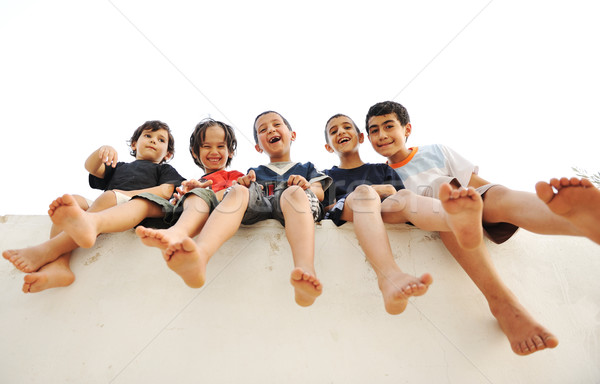 Children sitting on wall, happy boys laughing Stock photo © zurijeta