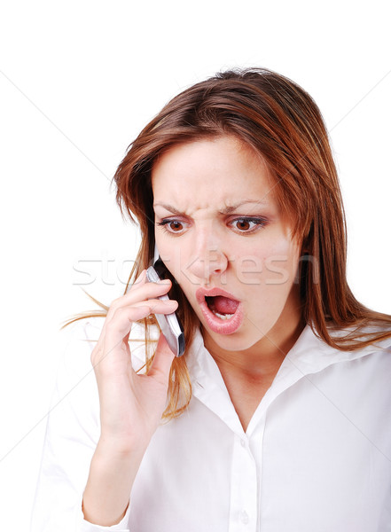 Young brunette with angry expression on face speakin on cell phone Stock photo © zurijeta