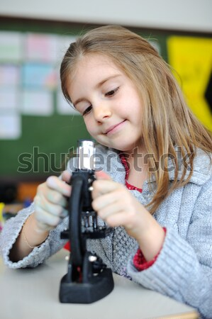 Beautiful young girl with a microscope Stock photo © zurijeta