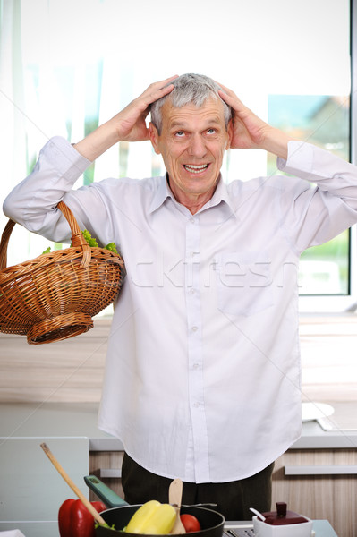 Good looking elderly man cooking  in kitchen Stock photo © zurijeta