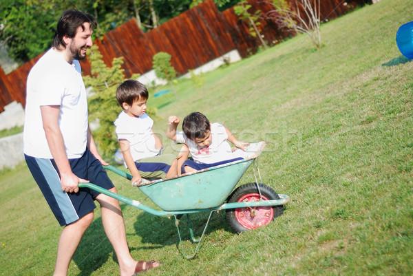 Pai branco condução meninos carrinho de mão céu Foto stock © zurijeta