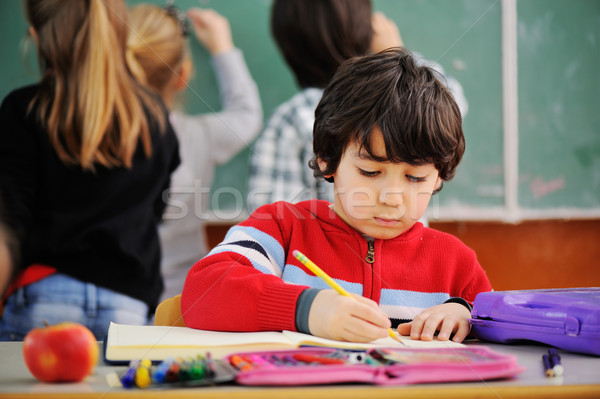 Portrait of lovely boy drawing in copybook at school Stock photo © zurijeta