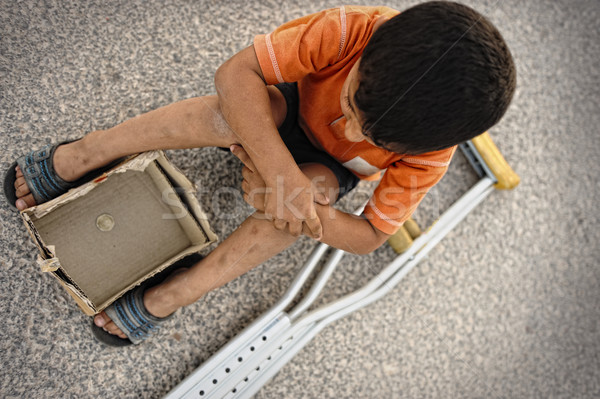 Hungry kid begging on the street with a crutches beside Stock photo © zurijeta