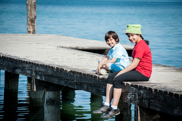 Stock photo: Girld and boy on lake dock in Italy
