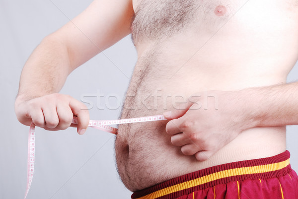 Fat man holding a measurement tape against white background  Stock photo © zurijeta
