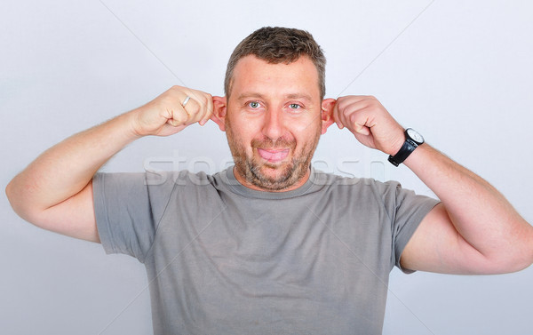 Young funny man holding his ears Stock photo © zurijeta
