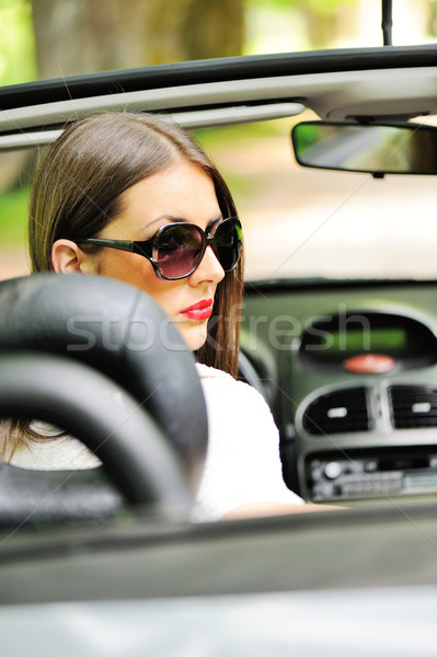 Portrait of young smiling woman siting behind steering wheel ins Stock photo © zurijeta