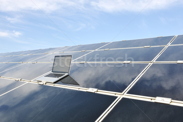 Laptop on  photovoltaic solar panels against blue sky Stock photo © zurijeta