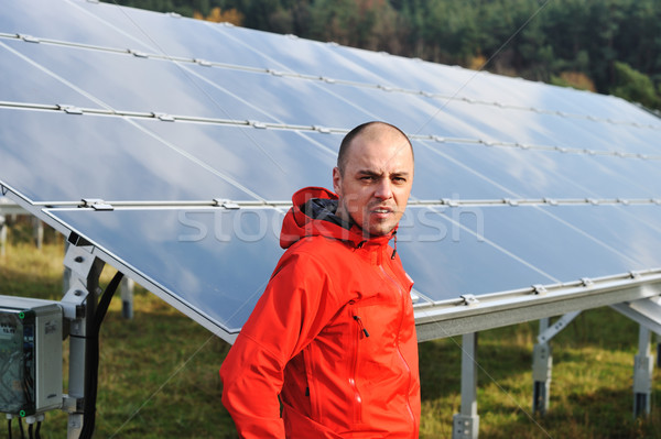 Stock photo: Young male worker with solar panels in background
