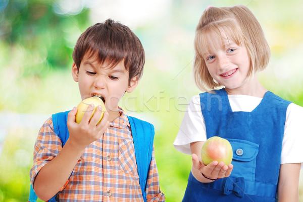 Two very cute children eating fruits outdoor Stock photo © zurijeta