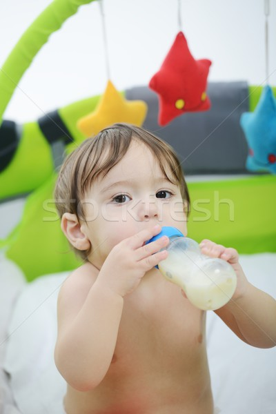 Beautiful little baby with a milk bottle in bed Stock photo © zurijeta