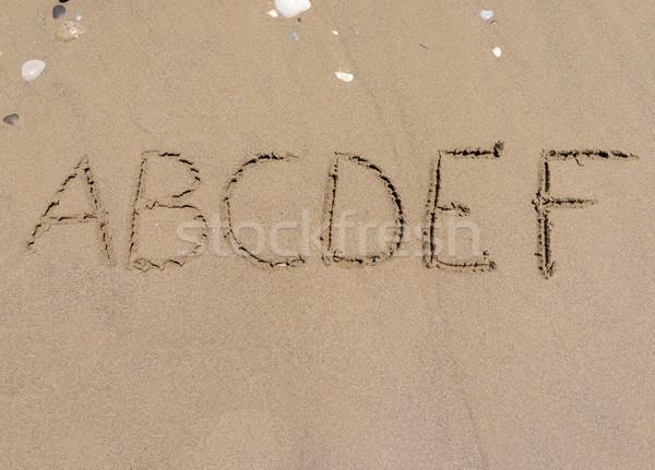 Sand alphabet letters handwritten on beach Stock photo © zurijeta