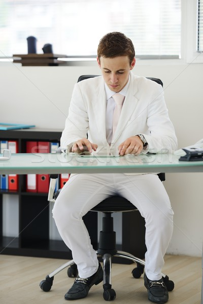 Young manager sitting at desk in bright office working on laptop Stock photo © zurijeta