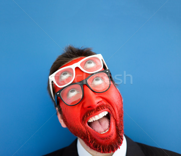 Red smiling man with double glasses and eyes looking up over blu Stock photo © zurijeta