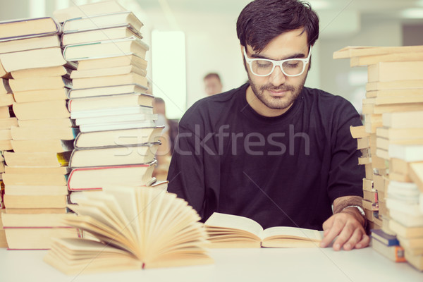 Middle eastern young student studying in college library with st Stock photo © zurijeta