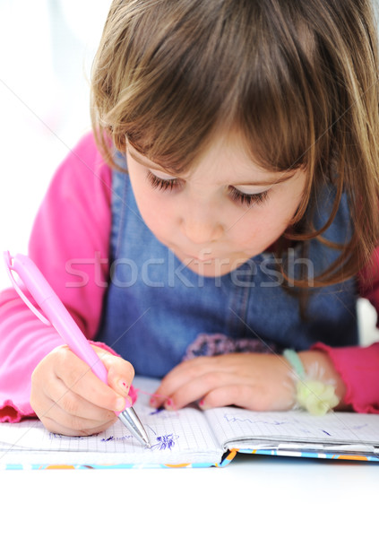 Stock photo: Happy little girl drawing with pencils at home