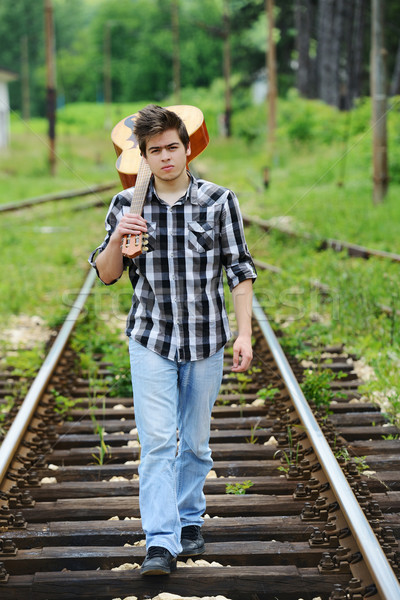 Handsome guy with guitar on a railroad Stock photo © zurijeta