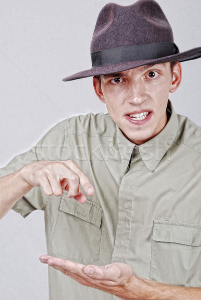 Young mane with hat is pointing with finger Stock photo © zurijeta