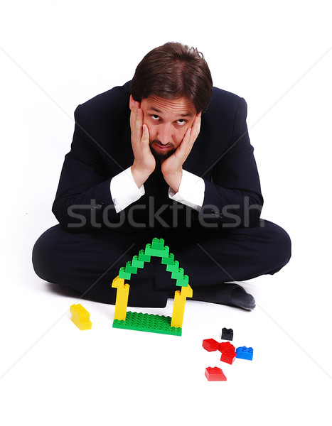 Young mane wearing suit is making a house with cubes toys Stock photo © zurijeta