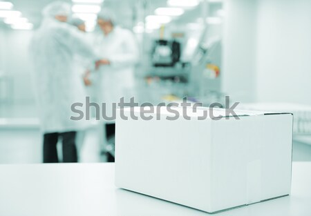 White box at automated production line at modern factory, people working in background Stock photo © zurijeta
