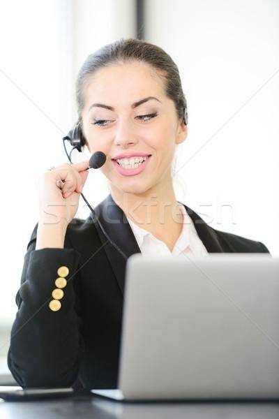 Female call centre employee speaking over the headset Stock photo © zurijeta