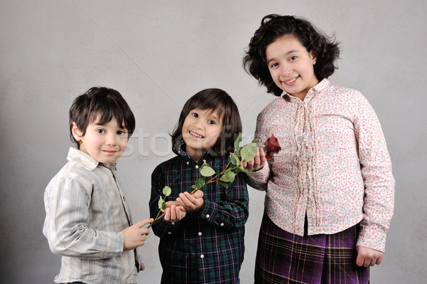 Two brothers and sister with beautiful red rose Stock photo © zurijeta