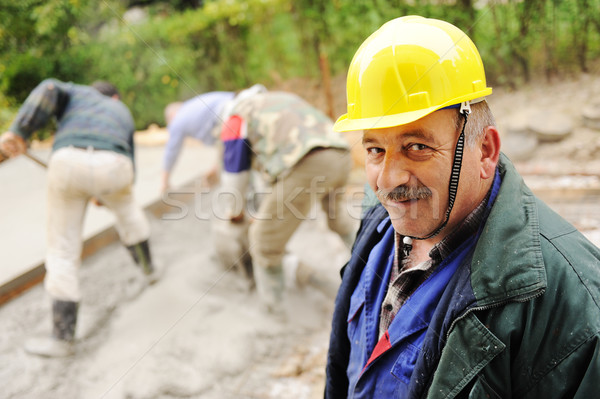Elderly menager on workplace with workers on fresh concrete Stock photo © zurijeta