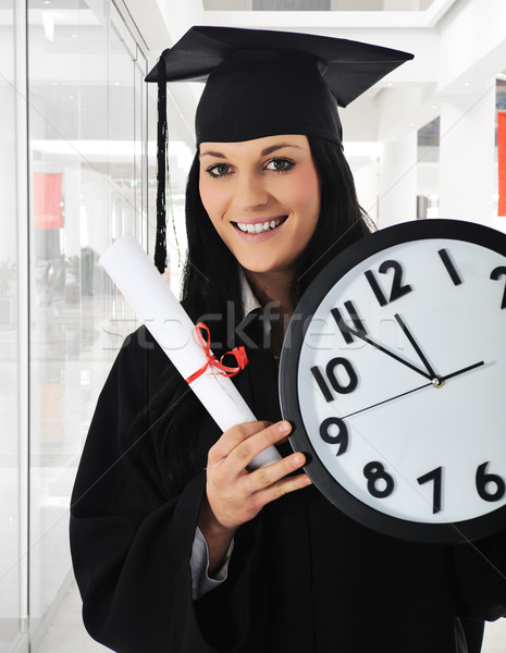 Stock photo: Graduating girl with diploma holding a watch