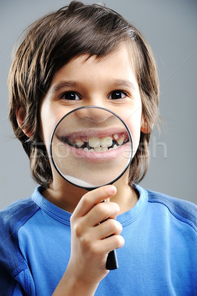 Portrait of child looking closely with magnifying glass Stock photo © zurijeta