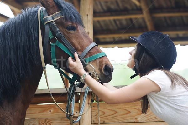 Beautiful girl riding taking a care of a horse Stock photo © zurijeta