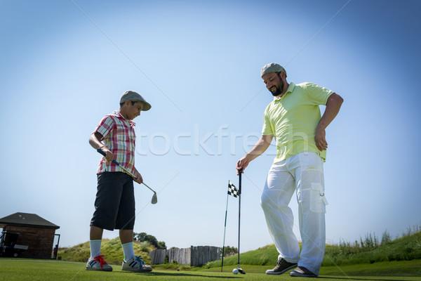 Father teaching son playing golf at club Stock photo © zurijeta