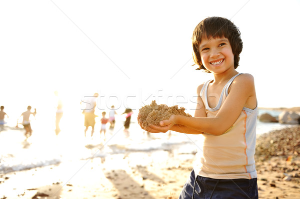 Kid on beach in sand playing, people around, summer hot nice time Stock photo © zurijeta